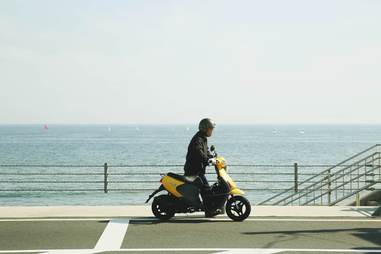 man riding yellow scooter