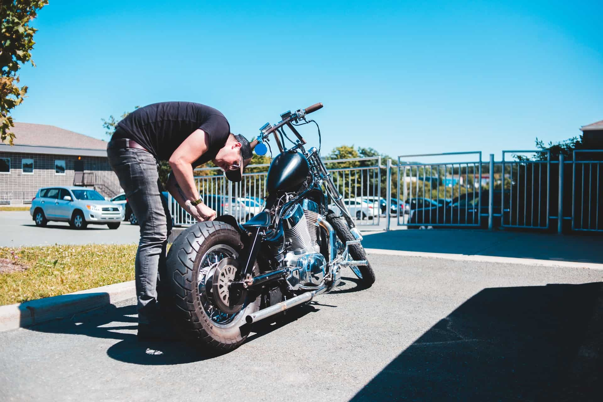 sunny day man checking tire