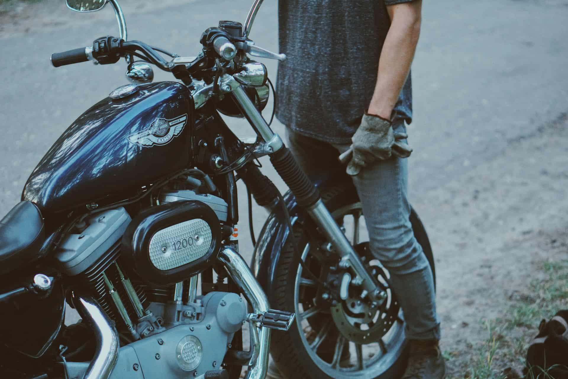 man fixing motorcycle beside road
