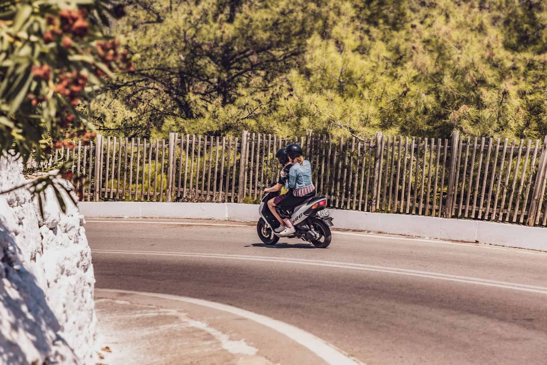 couple riding motorcycle curve