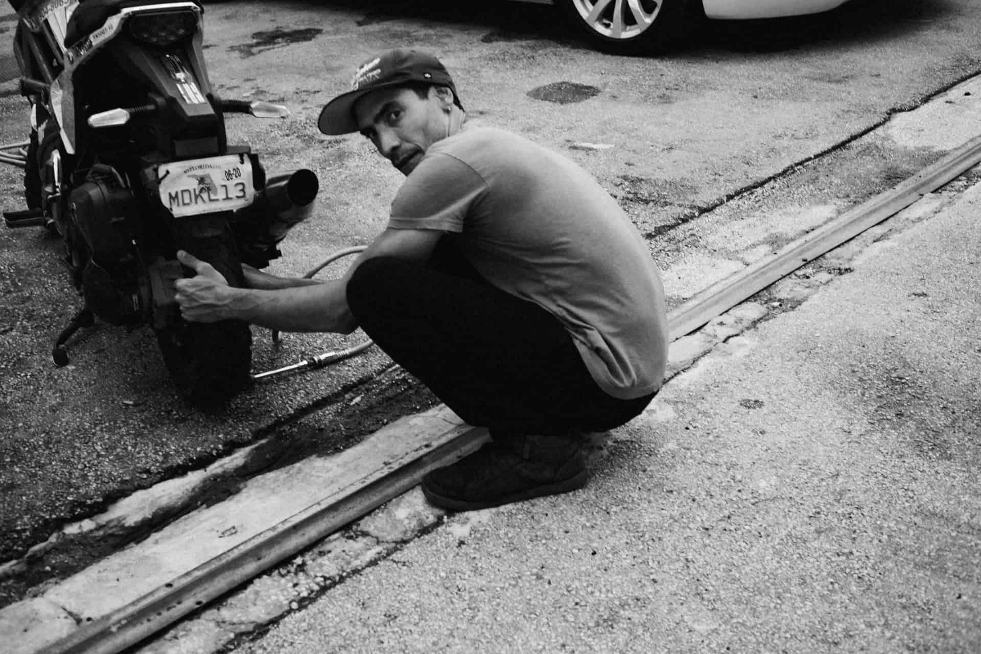 monochrome man changing tire
